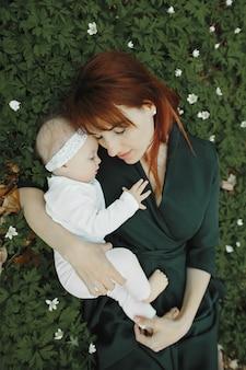 Счастливая мать и дочь лежат на траве