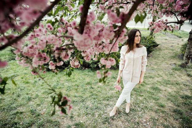 女の子は夢のような外観を持ち、公園の中に立っています。