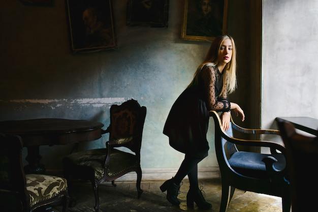 Девушка опирается на винтажный стул в кафе