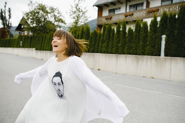 Улыбающаяся девушка бежит в белой одежде с мужским портретом