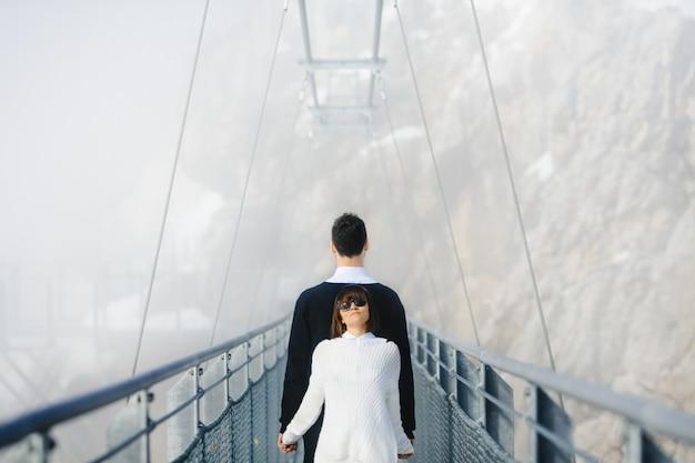 Мужчина и женщина стоят спиной к спине на высоком веревочном мосту