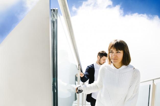 Жена и муж поднимаются по лестнице в небе