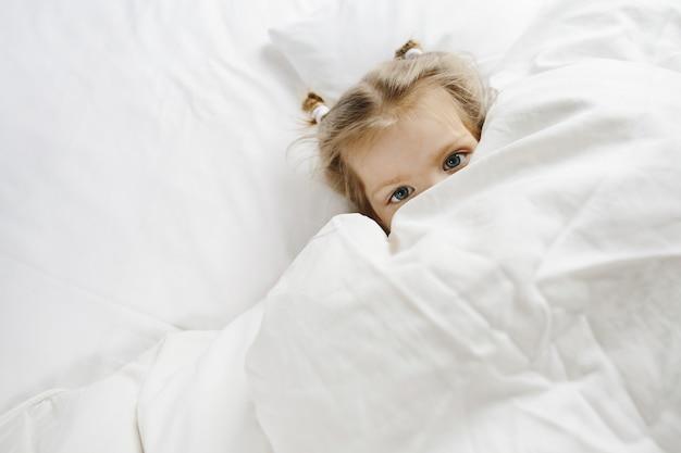 小さな女の子はベッドに隠れた