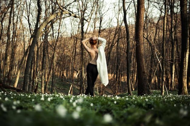 美しい少女は森と自然を楽しんでいます