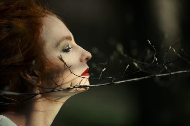 美しい赤毛の女の子は森の中で自然を楽しんでいます