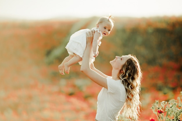 Мать держит ребенка на высоте на маковом поле