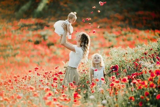 母は彼女の赤ちゃんを高さで保持し、彼女の長女はケシ畑で笑顔