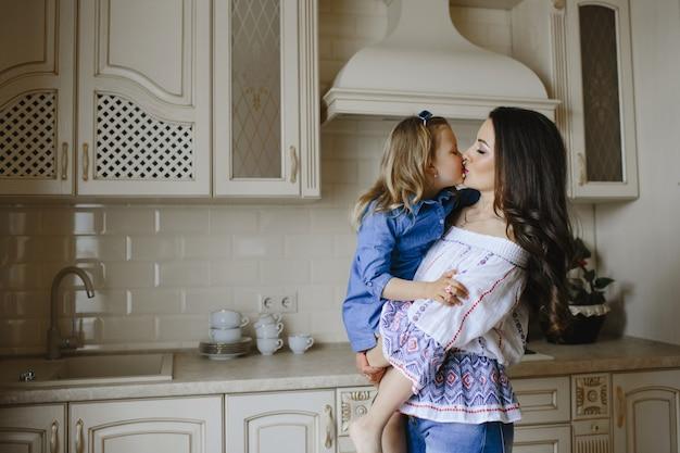 Мама целует маленькую дочку на кухне