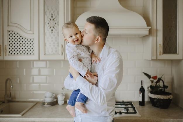 お父さんは台所で赤ちゃんの息子にキスします。