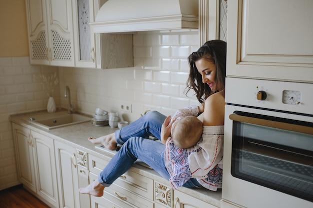 笑顔の母親が彼女のキッチンで赤ちゃんを抱いています