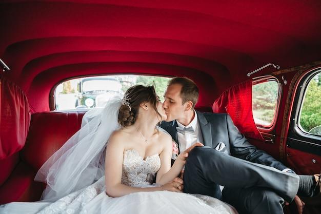 幸せな花嫁は車の中でキスしています