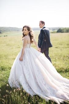 幸せな花嫁は夏にフィールドを歩き回っています
