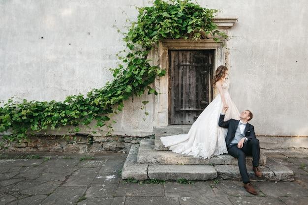 古い家の近くで美しい花嫁が撮影されています