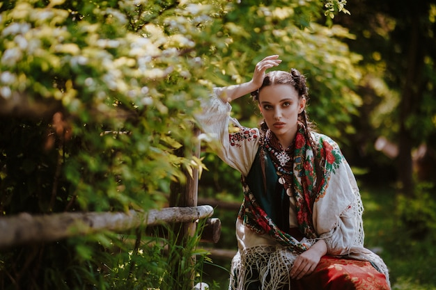 Молодая девушка в традиционном украинском платье сидит на скамейке в парке
