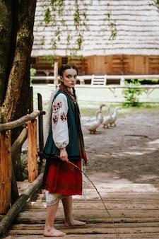 若い女の子は、伝統的な刺繍のドレスで裸足で歩く