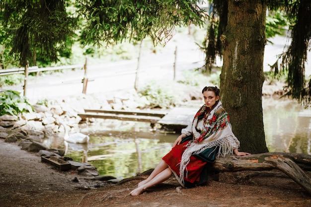 湖の近くのベンチに座っているウクライナの刺繍のドレスで美しい少女