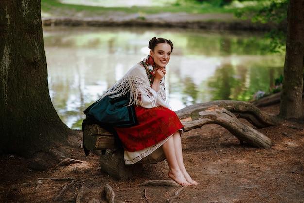 Молодая девушка в этническом вышитом платье сидит на скамейке возле озера