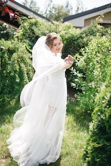 Красивая и улыбающаяся невеста в саду
