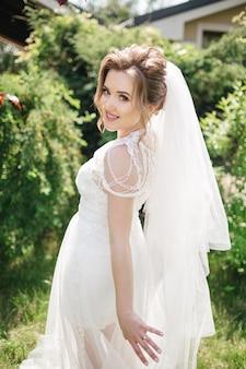 Улыбающаяся невеста гуляет в саду