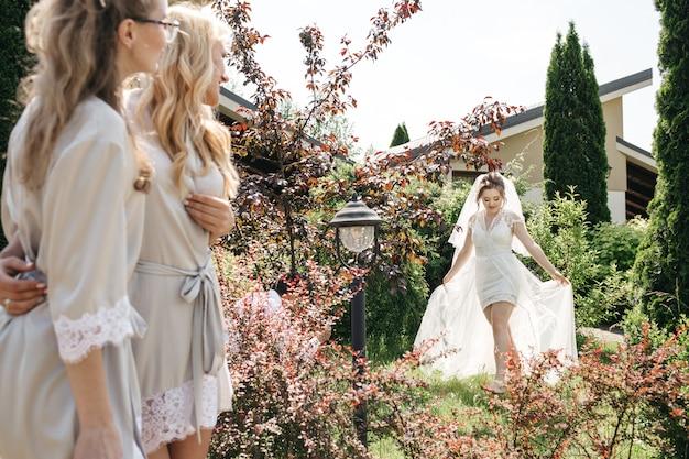Невеста и ее друзья гуляют в солнечном саду