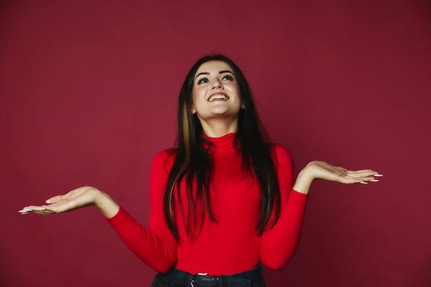 赤いプルオーバーに身を包んだ幸せな美しいブルネット白人少女はトップを探しています