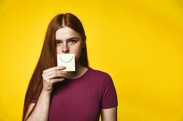Молодая рыжая девушка с серьезным видом держит открытку с улыбкой