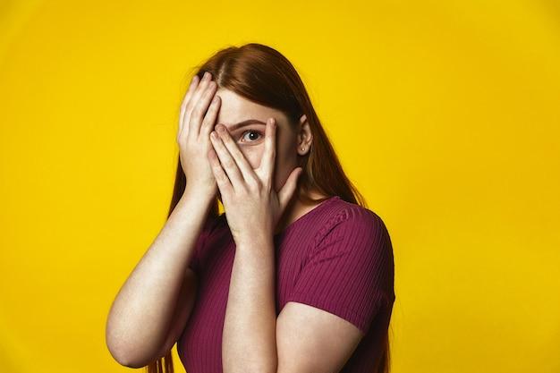 Молодая рыжая кавказская девушка закрывает лицо руками и смотрит сквозь пальцы