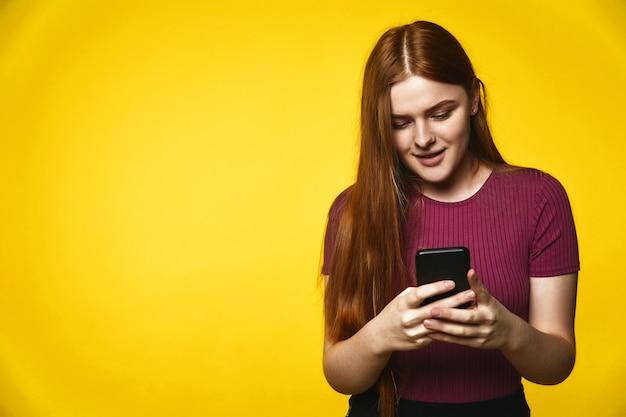 Молодая рыжая кавказская девушка счастливо смотрит на мобильный телефон