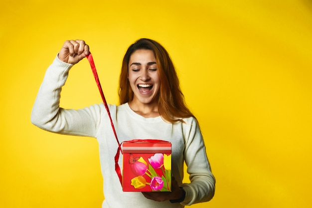 Молодая девушка распаковывает подарок и очень счастлива