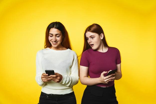 Две улыбающиеся кавказские девушки с современными смартфонами смотрят на экран телефона