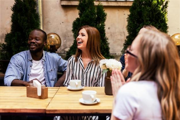 Африканский мальчик и кавказские девушки смеются в уютном кафе на открытом воздухе в жаркий солнечный день