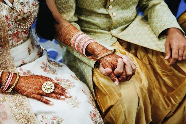 インドの結婚式のカップルが手を繋いでいます。