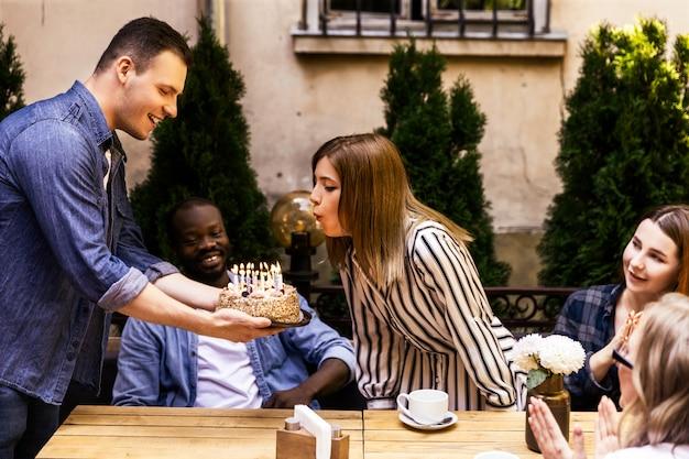 Торт ко дню рождения с горящими свечами, которые горит девушка и лучшие друзья на террасе уютного кафе