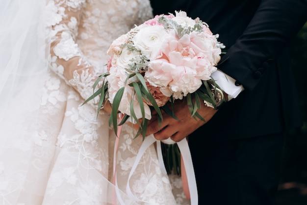 新郎と新婦が一緒に結婚式のピンクの花束を保持しています。