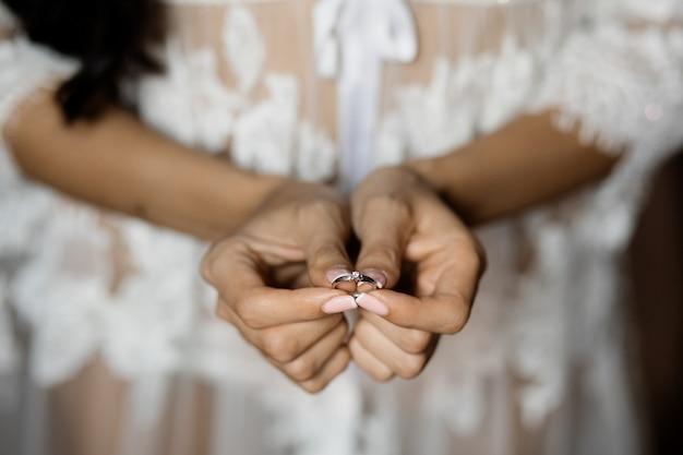 女性は繊細な宝石で彼女の婚約指輪を示しています
