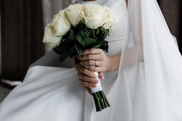 花嫁は彼女の手で上品な白いバラの花束を保持しています。