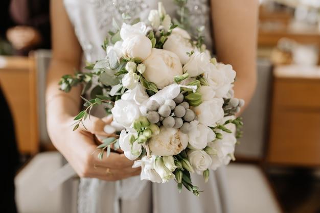 花嫁は白牡丹と緑の装飾が施された美しいブライダルブーケを持っています