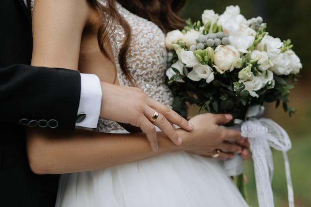 Невеста держит красивый букет, а жених обнимает ее за спину