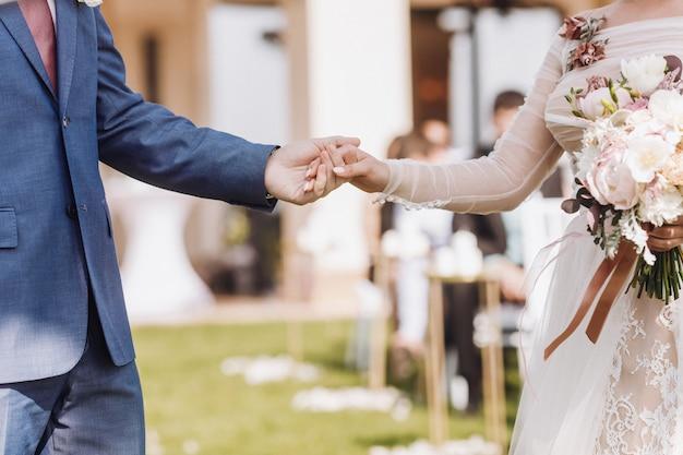 美しい結婚式のカップルを持っている手