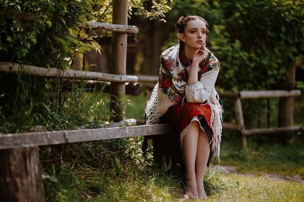 Красивая женщина в вышитом традиционном платье сидит на скамейке и смотрит вдаль