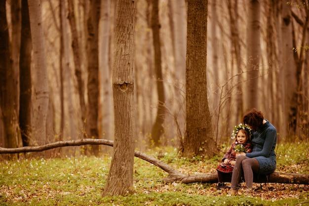 Мать с дочерью, сидящей на сундуке