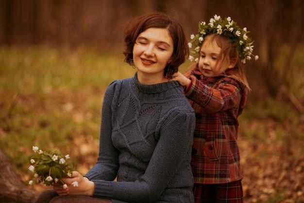 Дочь обнимает мать в парке