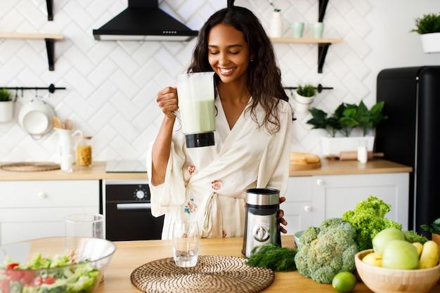 幸せなアフリカの女性はミルクセーキを飲むつもりです