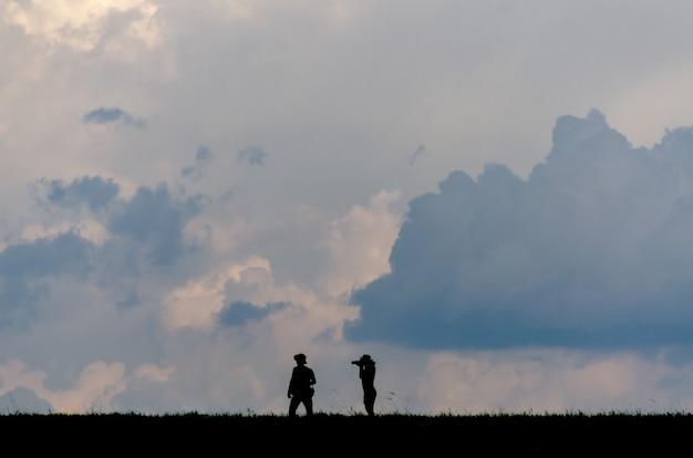 Силуэт людей фотографируют на открытом воздухе