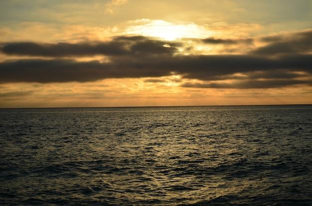 Вид на закат с заходом солнца за морем