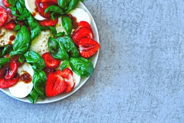 夏のカプレーゼサラダ。イチゴとカプレーゼ。バジルとモッツァレラチーズの食事療法のサラダ。ケトダイエット
