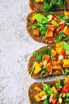 Тост с тыквой и рукколой. открытые бутерброды с тыквой. здоровые веганские тосты с зеленью и тыквой. осенняя закуска. брускетта с рукколой и тыквой.