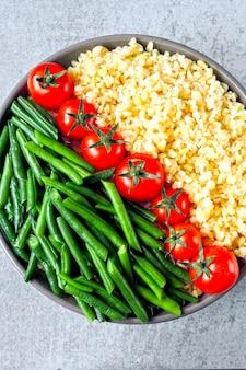 ブルガー、チェリートマト、インゲンのビーガンボウル。ボウルに健康食品。ビーガンランチボウル。
