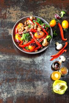 ブロッコリー、マッシュルーム、赤パプリカの温かいサラダ。スタイリッシュなぼろぼろの背景に温かい野菜とビーガンボウル。健康食品。キノコと野菜を使ったフィットネスランチ。