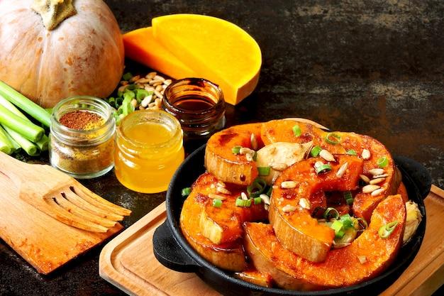 Запеченные ломтики тыквы в небольшой чугунной сковороде. рецепт запекания тыквы. горячий веганский обед.